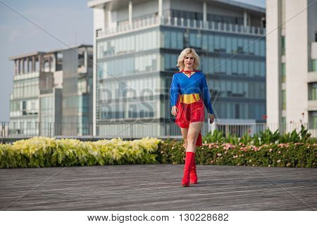 Attractive confident superwoman walking outdoors: female power