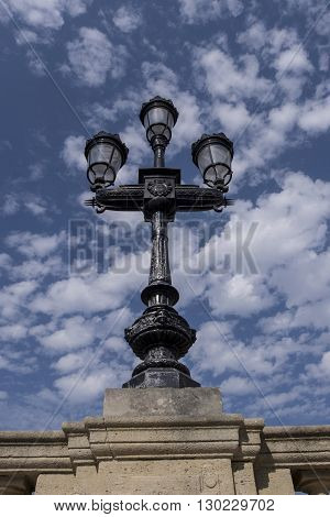 Bordeaux lamppost in black iron against blue sky