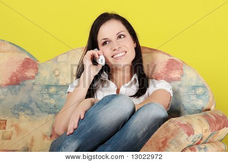 Young woman at home, talking by phone
