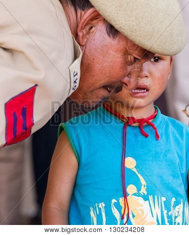 Leh, India - August 7, 2012: Military man comforting a crying baby boy at the His Holiness the 14th Dalai Lama teachings in Leh, Ladakh, Jammu and Kashmir, India