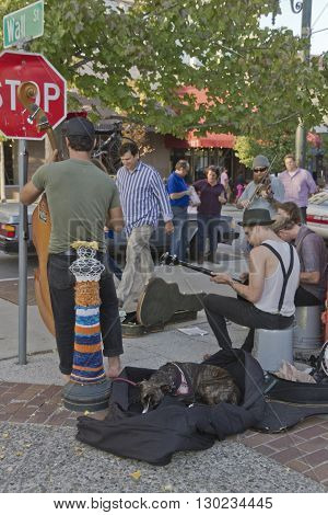 Asheville, North Carolina, USA - November 6, 2015: Street musicians play for tips and the enjoyment of a crowd of onlookers and tourists next to the Flat Iron statue and a colorful knit covered pole on Wall Street in downtown Asheville, NC