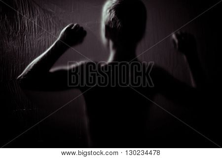 Rear View Of Child With Raised Fists In Darkness