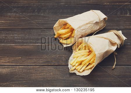 Tasty potato wedges and french fries wrapped into brown kraft wrapping paper. Fast food take away at rustic wood background. Choice of fried potatoes at wood. Chips, potato slices. Top view, copyspace