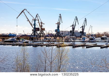 SAMARA RUSSIA - APRIL 24 2016: Silhouette of port cranes against the blue sky and motor boats at the Samara river port
