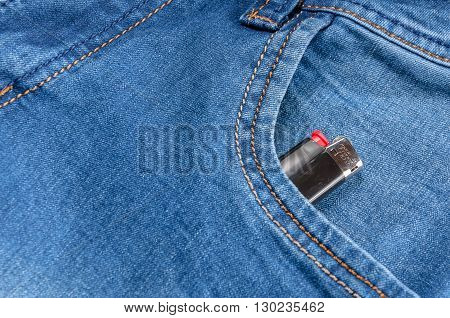 The pocket of jeans with lighter. Cloth background.
