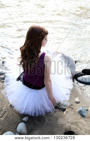 Beautiful girl wearing a white tutu by the river