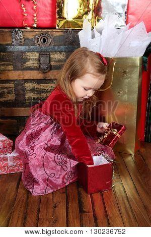 Little girl wearing a christmas dress looking at gifts