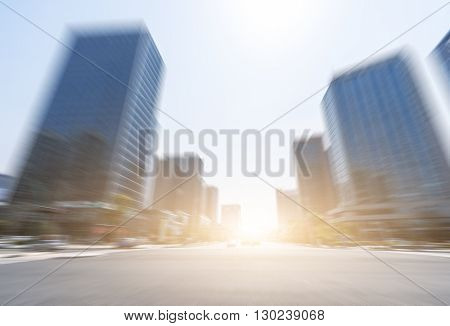 traffic on road intersection near modern office buildings at sunrise
