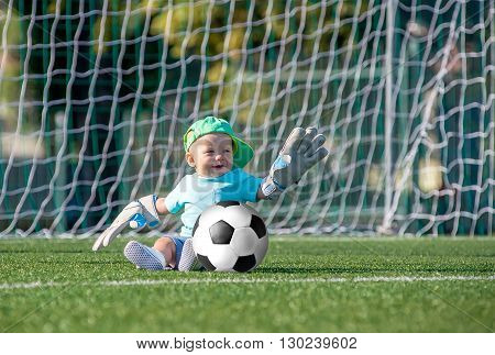 Merry tot sits with Ball on a football field in the cap. Football Championship 2016.
