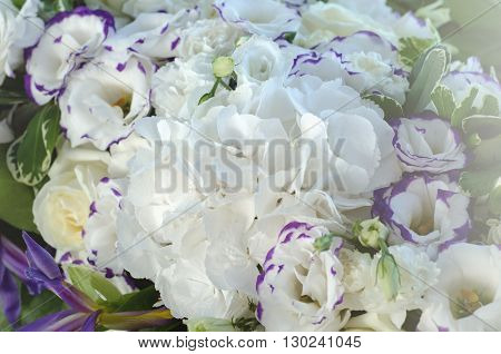Rich white hydrangea, delicate cream roses, purple eustoma, lush leaves in a beautiful decoration. Big bouquet of fresh flowers on a luxury wedding table. Summer background.