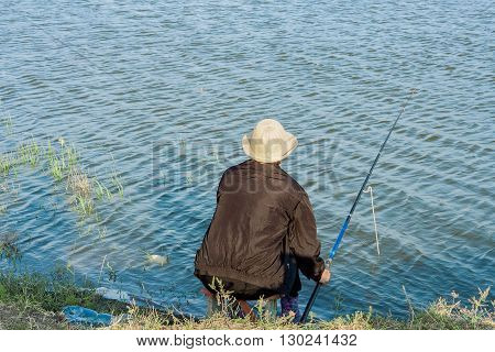 Fisherwoman in a white hat and a black tracksuit fishing for bait at sunset on the banks of the river