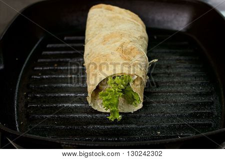 Mexican food burrito on frying pan, close up view
