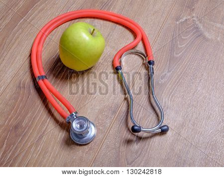 Stethoscope and apple isolated on wooden table