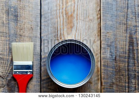 painting  with can of blue paint  and red brush on wooden background top view