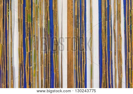 Colorful bamboo fence on wood texture for background.