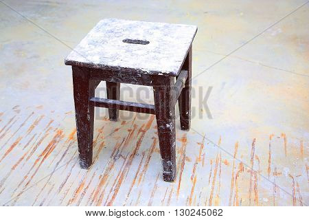 Dirty brown stool in the empty room