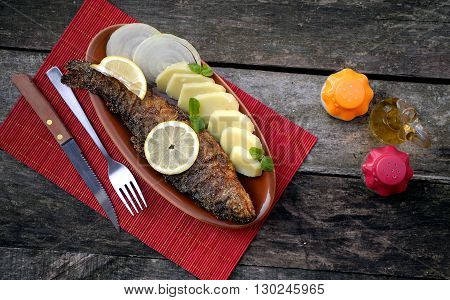 Baked trout fish with potatoes and onion
