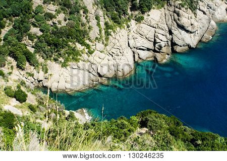 Rocky shore and clear blue sea in the hot summer.