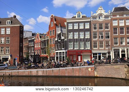AMSTERDAM, NETHERLANDS - MAY 4, 2016: People in outdoor cafe and old houses of traditional architecture along a canal in Amsterdam, Netherlands. Amsterdam is the capital and most populous city of the Netherlands.