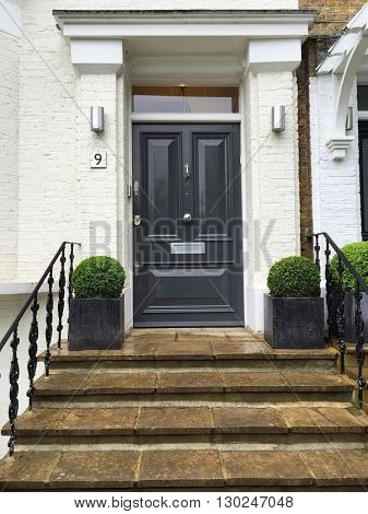 LONDON - MAY 18: Smart house entrance with grey front door and topiary bushes on May 18, 2016 in Hampstead, London, UK.