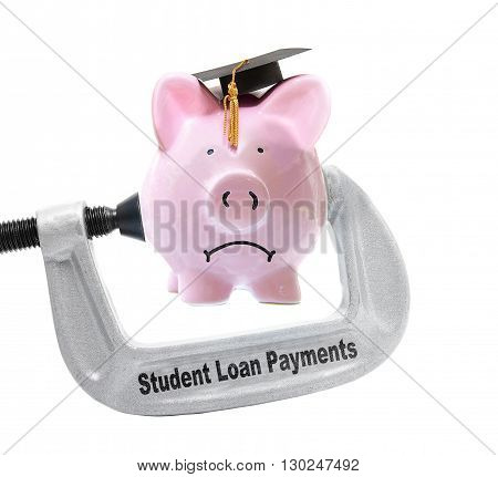 Frowning piggy bank wearing graduation cap being squeezed in a Student Loan Payments vice on white -