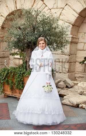 Bright sunshine and windy weather is the backdrop for a lovely bride holding a colorful bouquet of flowers.