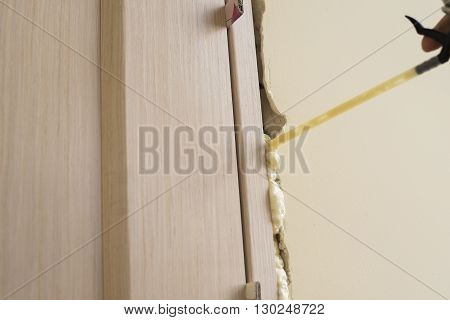 Installation of doors using polyurethane foam mounting. Cylinder Foam. Small depth of field