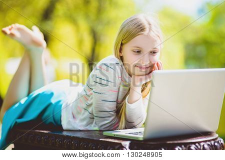 girl looking at a laptop lying on the bench at park outdoor.