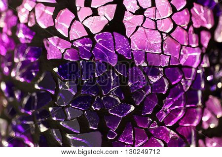 Purple glass fragments with a metal frame and backlight illumination.