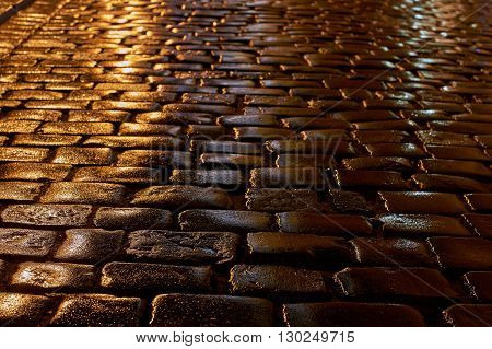 A wet cobbled street in the rain in Poznan