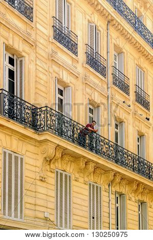 MARSEILLE FRANCE - JUL 18 2014: Man relaxing on a balcony on a very hot summer day in the center of Marseille