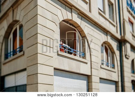 Tilt-shift photo of woman reading in her apartment iwth beautiful large windows on a warm spring day