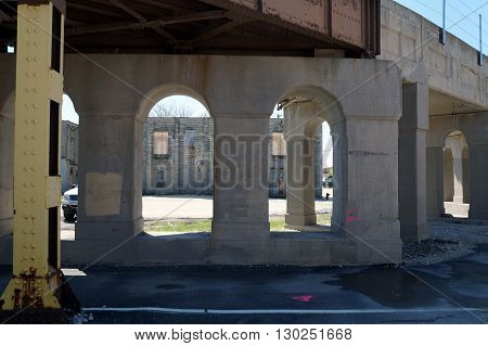 An abandoned building, as seen between the support columns of a railroad bridge, in downtown Joliet, Illinois.