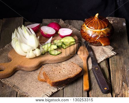 The cut vegetables on an old wooden table. Rural style close up dark background. A flower from a bulb radishes and a cucumber the cut with krudochka vegetable oil a knife bread