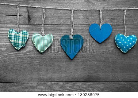 Wooden Background With Turquoise Hearts Hanging In A Row. Black And White Style With Colored Hot Spots. Copy Space For Advertisement Or Free Text. Greeting Card For Valentines Or Mothers Day