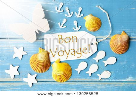 Flat Lay View Of Label With French Text Bon Voyage Means Good Trip. Sunny Summer Greeting Card. Butterfly, Shells And Fishes On Blue Wooden Background