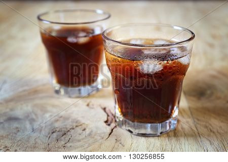 Cold fizzy cola soda with ice on wooden table