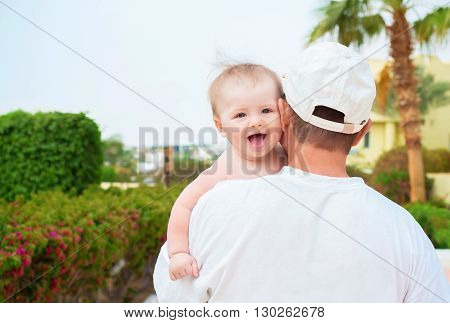 Funny baby on the father's shoulder shows tongue outdoor shot