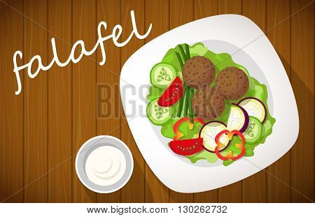 Plate of falafel with tzatziki sauce on wooden table. View from above.