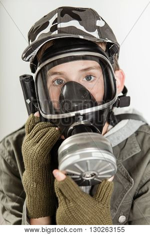 Child Holding Gas Mask Over Face