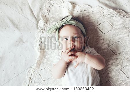 Portrait of a 4 month cute baby girl wearing lace flower headband and lying down on a crochet blanket