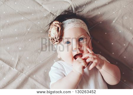 Portrait of a 4 month cute baby girl wearing lace flower headband and lying down on a bed with polka dot brown bedding, top view
