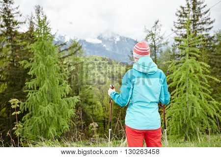 Woman wearing outdoor clothing (hardshell waterproof jacket and softshell pants) standing with trekking poles in hands and preparing for hiking tour in Bavarian Alps - exploring and adventure concept