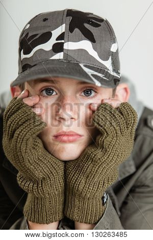 Male Teen Sulking While Holding Face In Gloves