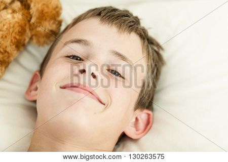 Top Down View Of Smiling Boy In Bed
