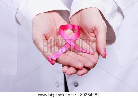 Woman doctor holding pink cancer breast ribbon in hands. Awareness of being sick. Close up.