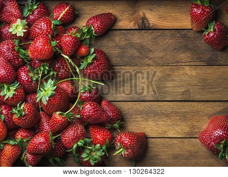 Summer fruit food frame. Strawberries over natural wooden background. Top view, copy space