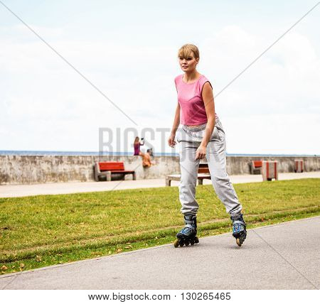 Outdoors activities sport and hobby.Wellbeing and exercising. Girl have fun riding rollerblades in park spending free time in summer.