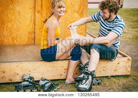 Sport injury. Couple of skaters outdoor. Young woman suffering from leg pain after taking a fall on the asphalt man is helping bandaging her injured knee