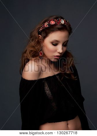 Passionate woman with long wavy hair dressed in black wearing beaded ruby garnet headpiece and earrings